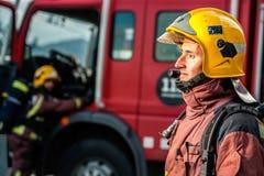 凝视在卡车前面的火的消防员 免版税库存照片