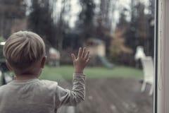 凝视在晚上光的一个窗口外面的小孩男孩入ga 库存照片