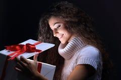 凝视在礼物盒的一个美丽的年轻浅黑肤色的男人的画象 免版税库存图片