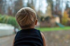 凝视在窗口外面的唯一小孩孩子 免版税图库摄影