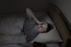 凝视天花板的成熟人在夜间期间,当在床上时 免版税图库摄影