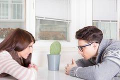 凝视彼此的夫妇横跨桌 免版税图库摄影