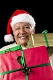 凝视横跨三件被包裹的礼物的年迈的绅士 库存图片