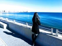 凝视海滩的美丽的girlin黑色礼服 幻想世界概念 免版税图库摄影