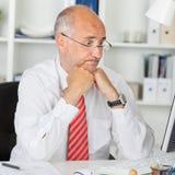 凝视计算机的迷茫的商人办公桌 图库摄影