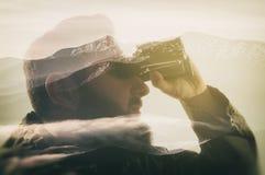 凝视通过双筒望远镜的时髦的有胡子的旅客特写镜头照片  免版税图库摄影