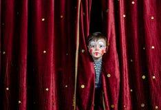 凝视通过阶段帷幕的男孩小丑 免版税库存照片