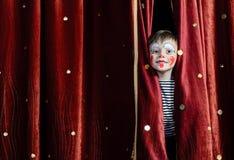凝视通过阶段帷幕的男孩小丑 免版税库存图片