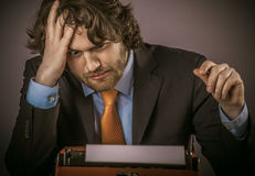 凝视他的打字机的沮丧的商人 免版税库存图片
