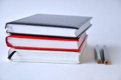 几个书或笔记本在一张桌上在白色背景 免版税图库摄影
