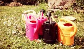 几个喷壶以各种各样的颜色在一个绿色庭院里站立每晴朗的夏日 免版税库存照片