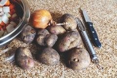 几个土豆和刀子在大理石工作台面说谎 免版税库存图片