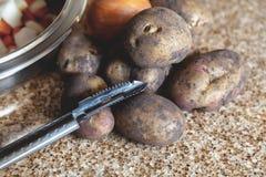几个土豆和刀子在大理石工作台面说谎 库存图片