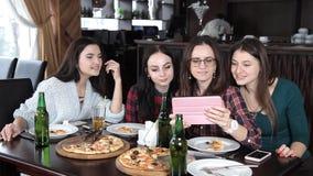 几个女孩在餐馆吃比萨并且喝从瓶的啤酒 谈话笑和庆祝 股票录像