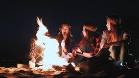 几个女孩由火坐在晚上并且油煎香肠 谈论并且带领交谈 在竞选来了 股票视频