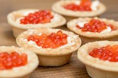 几个果子馅饼用红色鱼子酱和黄油在木棕色桌宏指令 免版税库存图片