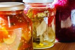 几个瓶子在一张木桌上的罐子菜 免版税库存照片