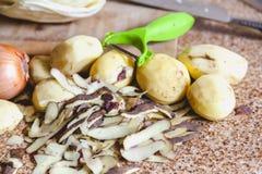几个被剥皮的土豆和果皮在大理石工作台面说谎 库存图片
