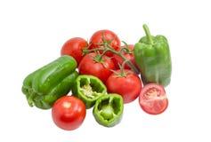 几个绿色甜椒和蕃茄在轻的背景 图库摄影