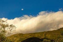 几乎满月在一朵密集的云彩上上升 免版税库存图片