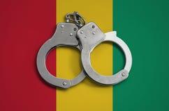 几内亚旗子和警察手铐 法律在国家和保护的遵守的概念免受罪行 库存照片