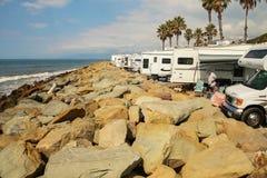 几围拢的两个人在Faria多岩石的海滩的RVs  库存照片