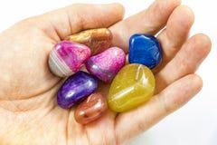 几块美丽和五颜六色的水晶石头在手上 免版税库存图片