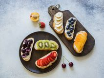 几多士用各种各样的莓果和果子和奶油乳酪在灰色背景 顶视图 库存图片