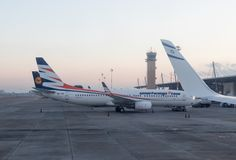 几家航空公司飞机在清早站立在机场主楼在国际本古理安airpor 免版税库存图片