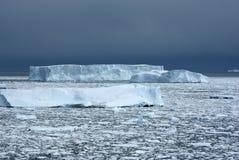 几座不同的冰山在海洋覆盖下午。 库存照片