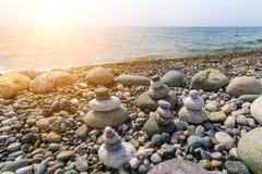 几座金字塔被堆积在海滩的小卵石在日落 图库摄影