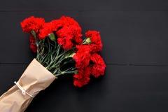 几支红色康乃馨静物画在黑背景的 图库摄影