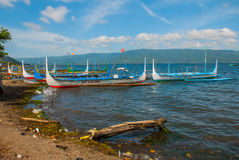 几条传统菲律宾舷外架小船或` banca `停泊了在Taal湖, Tagaytay菲律宾岸的一个木码头  库存图片