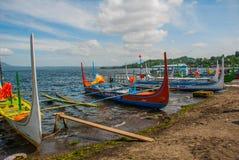 几条传统菲律宾舷外架小船或` banca `停泊了在Taal湖, Tagaytay菲律宾岸的一个木码头  图库摄影