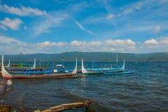 几条传统菲律宾舷外架小船或` banca `停泊了在Taal湖, Tagaytay菲律宾岸的一个木码头  库存照片