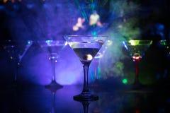几杯著名鸡尾酒马蒂尼鸡尾酒,在一个酒吧的射击与黑暗的被定调子的有雾的背景和迪斯科光 俱乐部饮料概念 免版税图库摄影