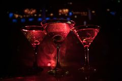 几杯著名鸡尾酒马蒂尼鸡尾酒,在一个酒吧的射击与黑暗的被定调子的有雾的背景和迪斯科光 俱乐部饮料概念 库存照片