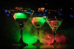 几杯著名鸡尾酒马蒂尼鸡尾酒,在一个酒吧的射击与黑暗的被定调子的有雾的背景和迪斯科光 俱乐部饮料概念 图库摄影