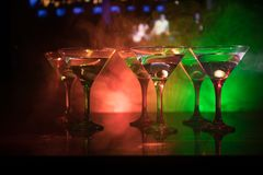 几杯著名鸡尾酒马蒂尼鸡尾酒,在一个酒吧的射击与黑暗的被定调子的有雾的背景和迪斯科光 俱乐部饮料概念 库存图片