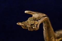 几枚硬币在镀金的手上 图库摄影