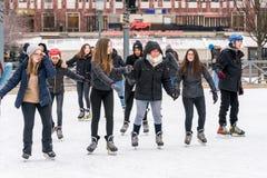 几滑冰在一个公开滑冰的溜冰场的愉快的少妇户外 库存照片