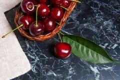 几片红色甜樱桃和大绿色叶子在桌上 Fres 库存图片