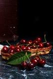 几片红色甜樱桃和大绿色叶子在桌上 Fres 免版税库存图片