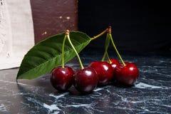 几片红色甜樱桃和大绿色叶子在黑暗的大理石bac 免版税库存图片