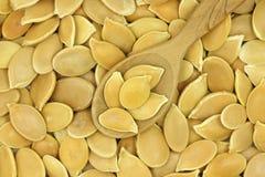 几粒金黄南瓜籽在木匙子背景中 免版税库存图片