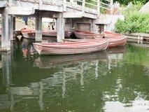 几艘木划艇停泊了在桥梁下 免版税图库摄影