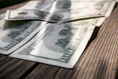 几100美元钞票关闭年迈的木表面上 免版税库存照片