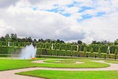 凡尔赛,法国2016年7月02日:在花床附近的喷泉 免版税库存照片