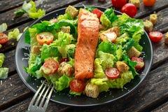 凯撒三文鱼沙拉用油煎方型小面包片、帕尔马干酪、蕃茄、选矿和胡椒在一个黑色的盘子在木桌上 免版税图库摄影