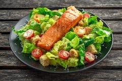 凯撒三文鱼沙拉用油煎方型小面包片、帕尔马干酪、蕃茄、选矿和胡椒在一个黑色的盘子在木桌上 免版税库存照片